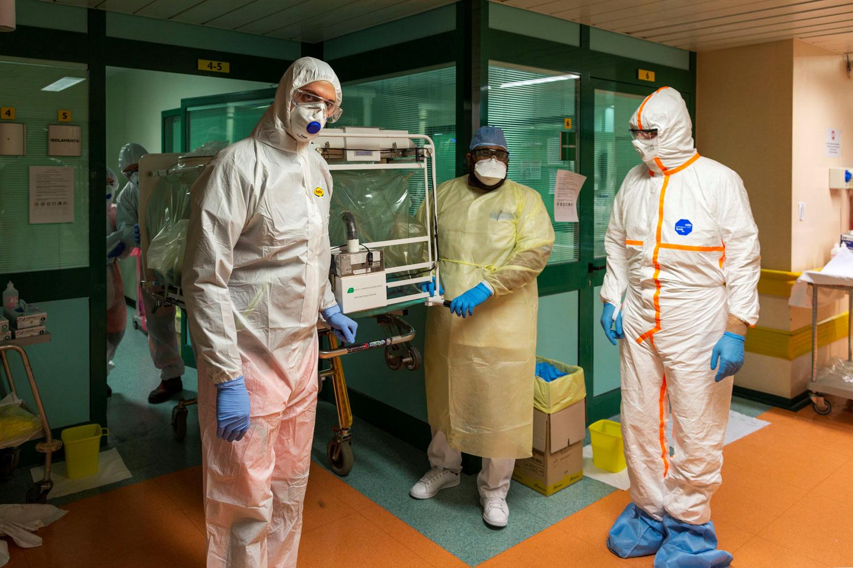義大利疫情嚴重,病人激增,醫院爆滿。圖為醫護人員把新冠肺炎病人送到羅馬一家醫院收治。(路透)
