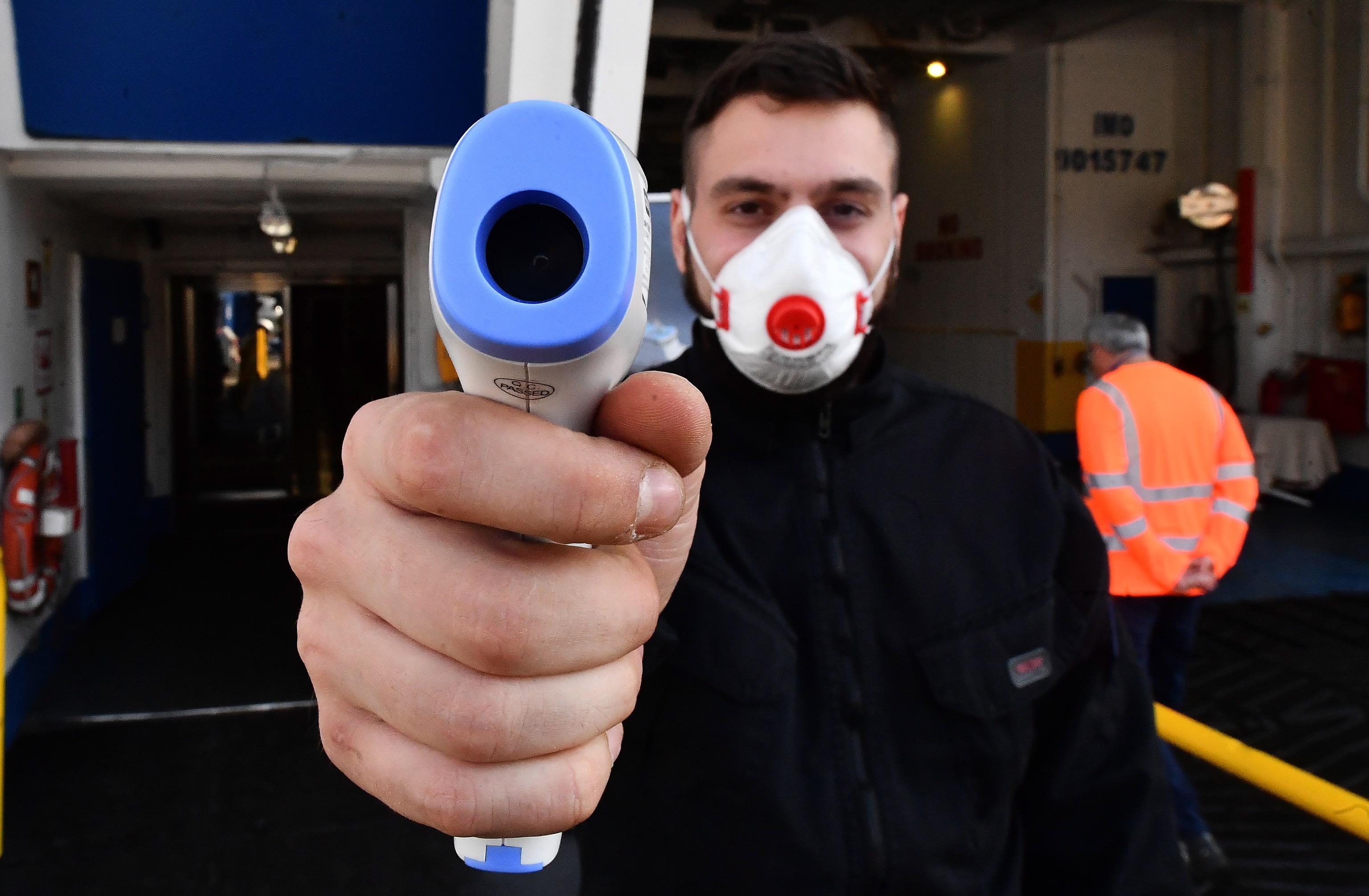 義大利成為中國以外疫情最嚴重國家,圖為義大利檢測人員在熱那亞一家醫院門口檢測體溫。(歐新社)