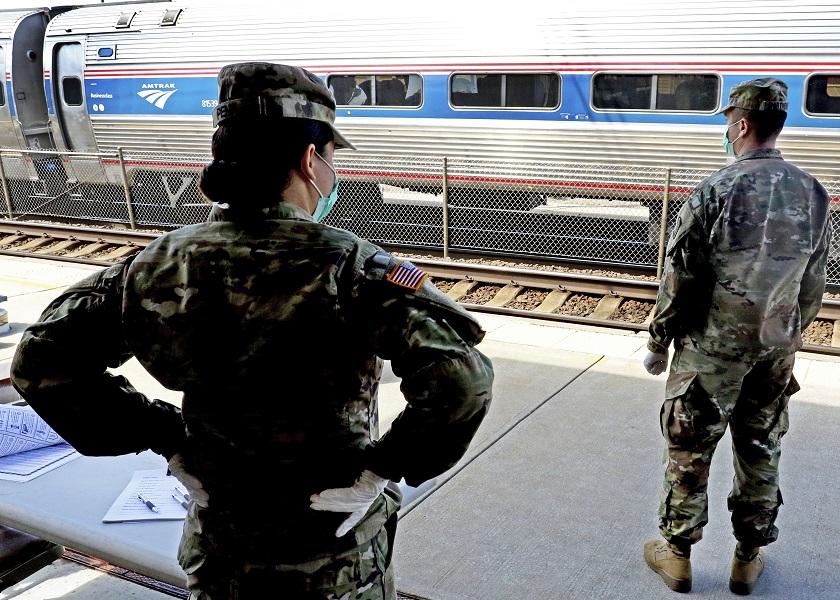 羅德島州長下令所有到該州避難的紐約人,都必須隔離14天。圖為羅德島州的國民兵在火車站檢查紐約來的旅客。(美聯社)