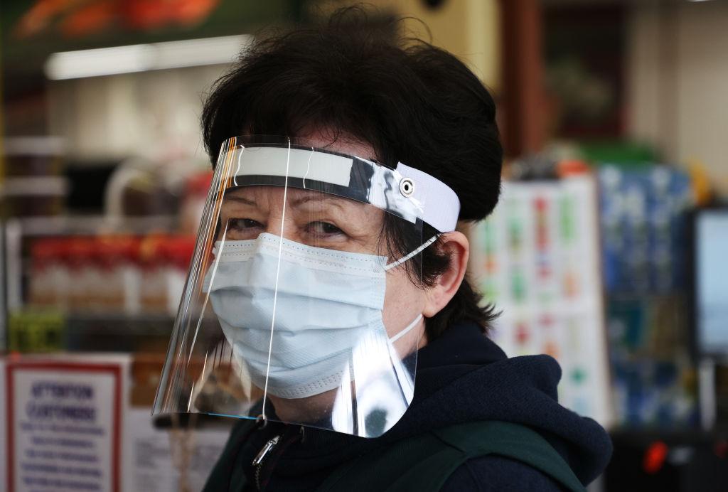 紐約一家便利店,收銀員工作時戴上了口罩和塑料製遮陽板。(Getty Images)