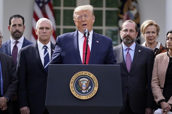 美國總統川普(中)13日召開記者會,宣布美國進入緊急狀態。(美聯社)