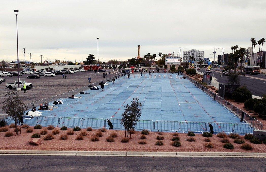官方原先在水泥地上,鋪上了一張張的藍色大地毯,但後來考慮到清潔與消毒不便,目前睡墊物資又供不應求,於是只好在水泥地上直接劃設白線網格,作為床位。(Getty Images)