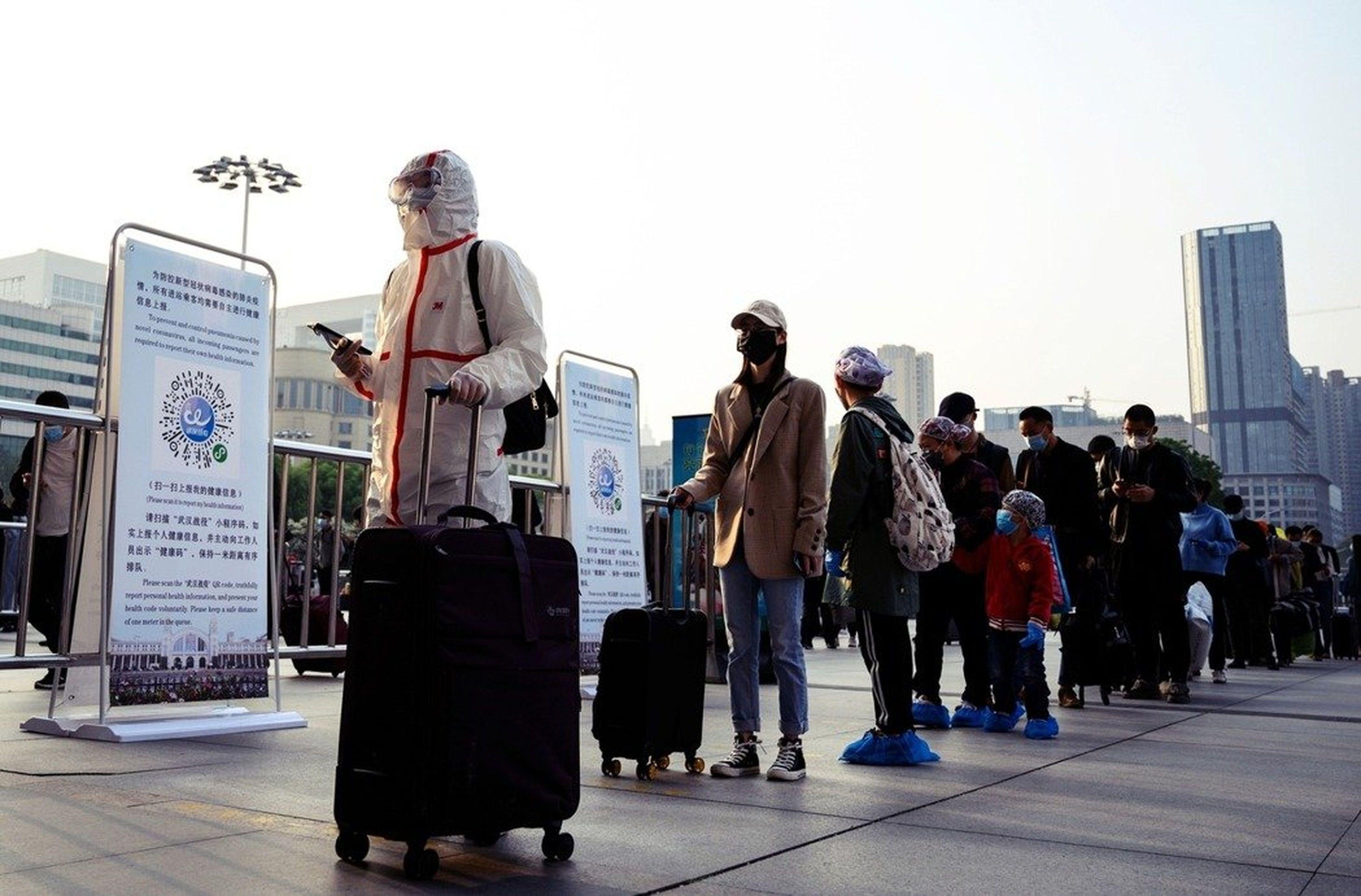 8日上午,在漢口站排隊準備離開的民眾,有的人依然穿戴整套的防護衣。防護衣底下,武漢人擔心「復工之後會不會被歧視?」(Getty Images)