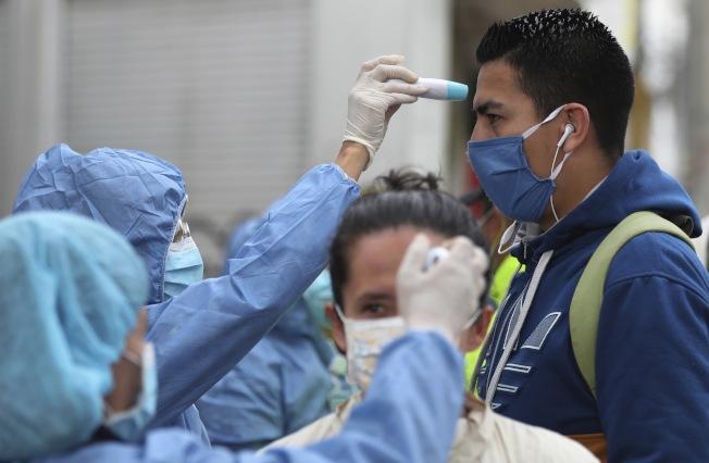 在哥倫比亞,護士為即將乘公交的民眾測體溫。(美聯社)