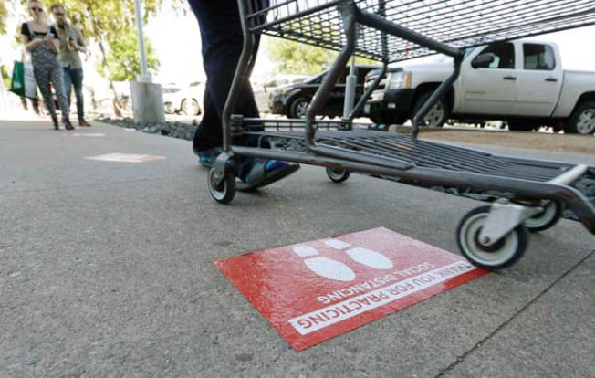 超市停車場地上,貼出告示,要人保持社交距離(social distancing)。(Getty Images)