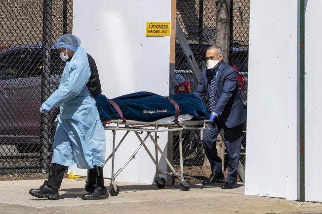 紐約州新冠病例死亡人數激增,圖為醫護人員推走一名裝在屍袋內的過世病人。(Getty Images)