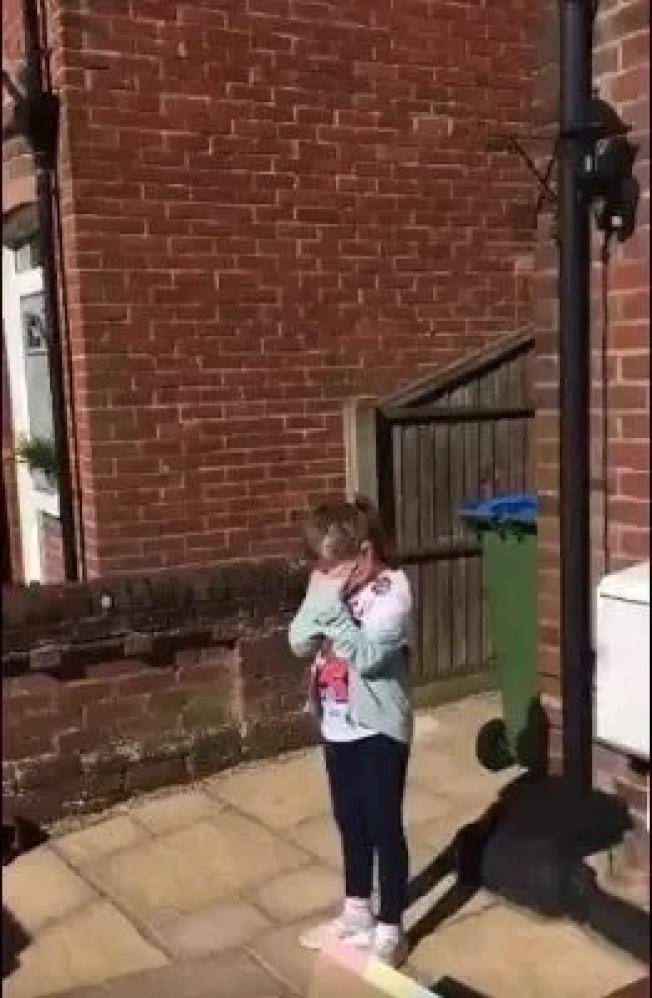 八歲小女孩站到自家門口,接受街坊鄰居的生日歌祝福。(取材自推特)