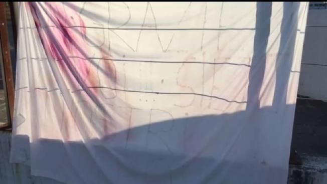義大利某家醫院的外牆掛著布條感謝醫護人員,錄下影片的人哭著口述白布寫「你是我們的英雄」。圖/截自靈醫會提供影片