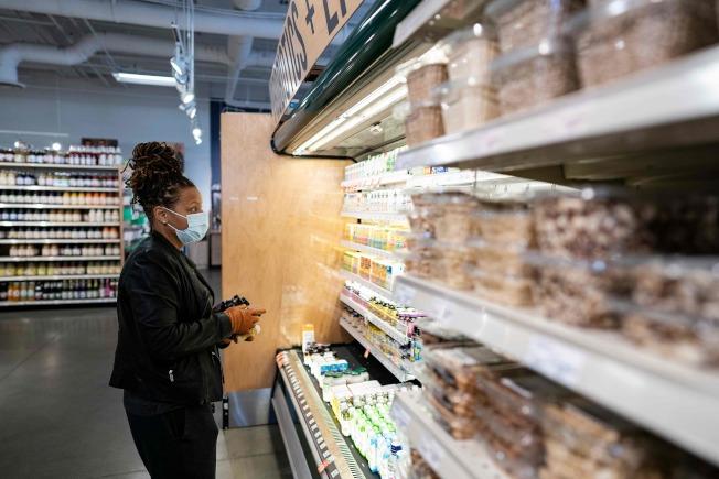 2日在華府,一民眾戴著口罩和手套在超市採購。(Getty Images)
