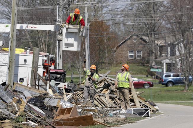 田納西州中部3月3日慘遭致命的龍捲風蹂躪,許多居民家毀人亡,新冠病毒又接踵而至。圖為電力公司工人修理電纜。(美聯社)