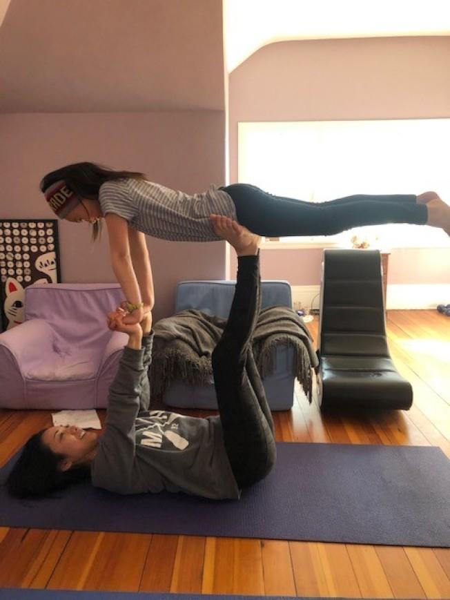 教授瑜伽的詹千香,居家避疫期間在家陪伴孩子一起做運動。(詹千香提供)