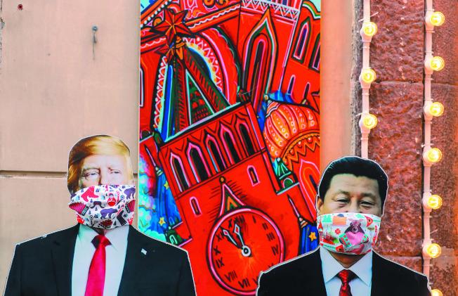 中美決定休兵以便對抗疫情。圖為俄國莫斯科一間紀念品店門口擺放戴口罩的美國總統川普(左)和中國國家主席習近平(右)人形立牌。(歐新社)