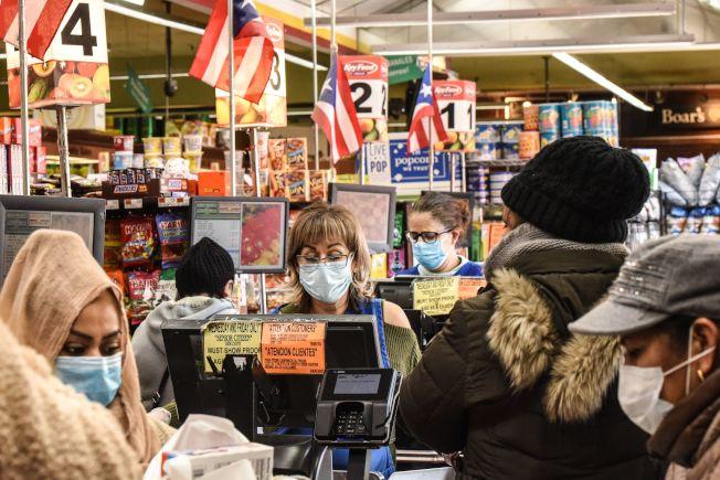 隨著疫情日益嚴重,在公共場所戴口罩的人越來越多,圖為紐約市布魯克林一家雜貨店的收銀員和顧客都戴上口罩。(Getty Images)