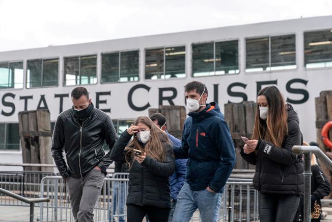 白思豪市長宣布,紐約市民在公共場所要遮住口鼻,圖為觀光客戴口罩在曼哈頓搭乘遊船。(路透)