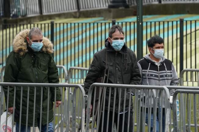 白思豪市長宣布,紐約市民在公共場所要遮住口鼻,圖為民眾戴口罩經過皇后區艾姆赫斯特醫院前面。(Getty Images)