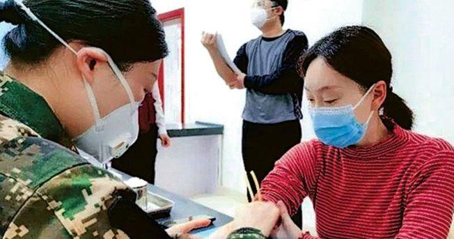 接種疫苗後的第七天,工作人員為靳官萍採血。(取材自澎湃新聞)