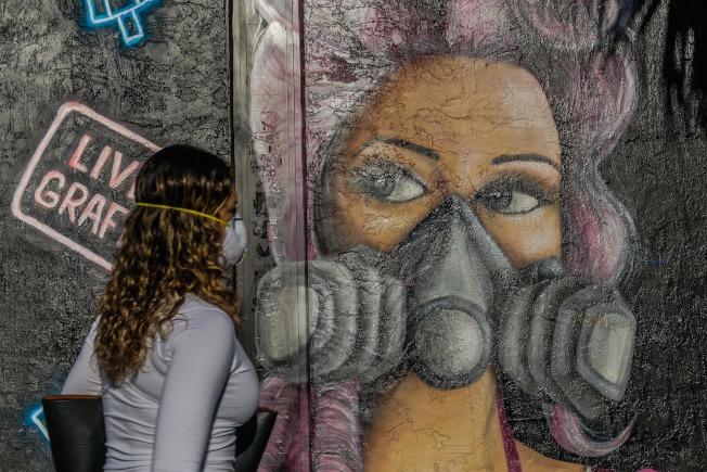 邁阿密一名女子行經一幅戴面罩的壁畫。(Getty Images)
