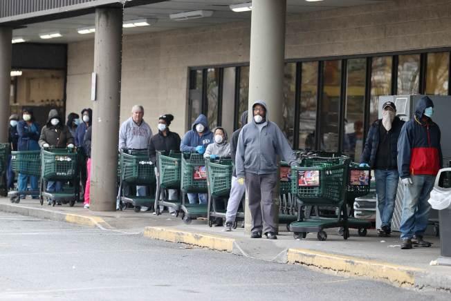 紐約州疫情嚴重,民眾已自發性戴上口罩,在一家超市外面排隊。(Getty Images)