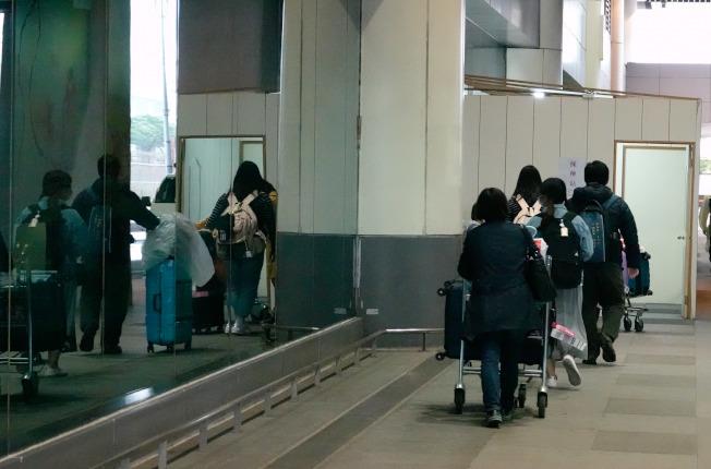 入境旅客有症狀者必須集中檢疫,等待採檢結果。不少旅客在採撿站前排隊等候。(記者鄭超文/攝影)