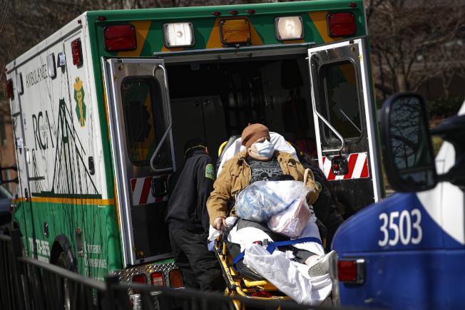 聯邦政府決定為無健保者支付新冠病毒醫療費用。圖為醫護人員把病患送到布魯克林醫療中心救治。(美聯社)
