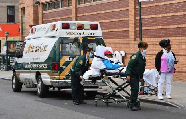 聯邦政府決定為無健保者支付新冠病毒醫療費用。圖為醫護人員把病患送到布魯克林醫療中心救治。(Getty Images)