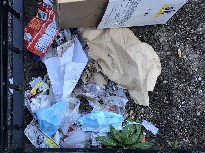 街邊種植樹木的圍欄上有許多口罩和手套連著其他垃圾堆積在一起。(記者顏潔恩/攝影)