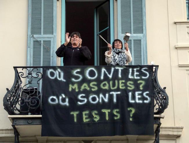法國尼斯市民4日敲擊廚具聲援醫護,掛起標語「口罩在哪裡?檢測在哪裡?」(路透)