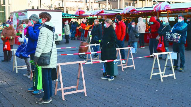 德國黑森邦哈瑙市民眾4日在當地市集一間肉店前排隊並保持距離,避免被他人傳染病毒。(路透)