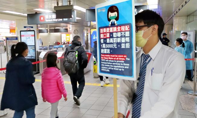 搭捷運必須全程戴口罩,台北捷運公司派人在各車站入口加強宣導這項新規定。(記者林俊良/攝影)