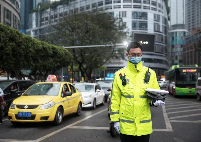 重慶渝中區執勤警察脫帽肅立默哀。(中新社)
