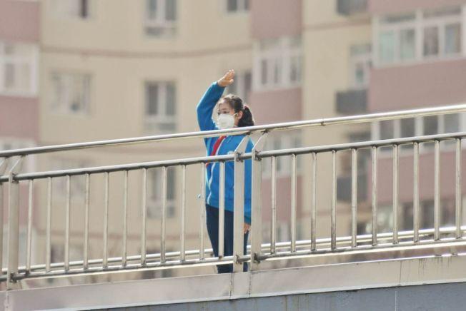 在蒲黃榆路口的天橋上,一位身著校服、佩戴著紅領巾的小姑娘莊嚴肅立,向著遠方敬起隊禮。(取材自北京日報)