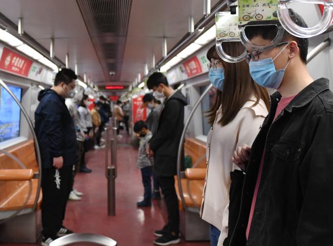 4月4日,北京地鐵車廂內的乘客起立默哀。 (新華社)