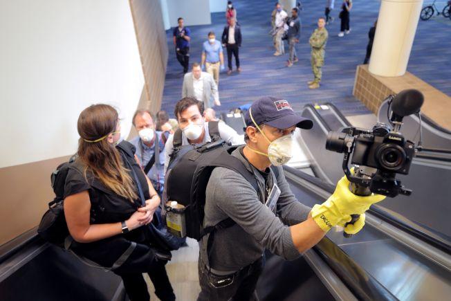 美國東南部疫情急速升高,圖為媒體戴上口罩及手套在紐奧良採訪。(Getty Images)