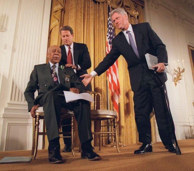 1997年,前總統柯林頓(圖右)正式向塔斯基吉研究受害者道歉。圖為柯林頓與前副總統高爾(圖左後)在記者會上協助當時已94歲的倖存者赫曼‧蕭(圖左前)。(美聯社)