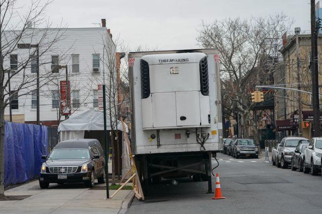 美國可能短報新冠肺炎死亡人數。圖為一輛黑色靈柩車抵達做為臨時太平間的冷凍貨櫃車旁,以便運送死者遺體。(Getty Images)