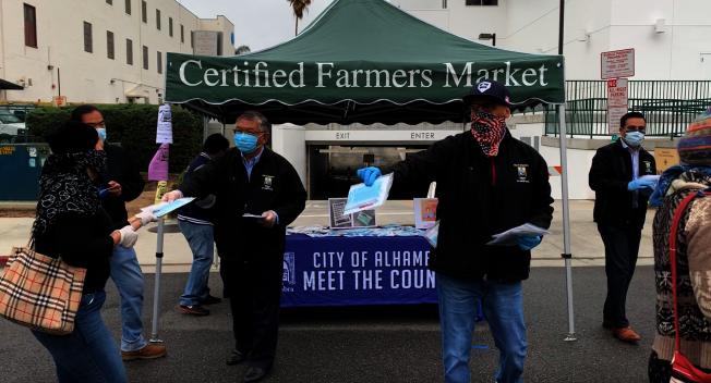 阿市前市長沈時康(左二)、副市長David Mejia(左三)向過路民眾發放口罩。(記者陳開/攝影)