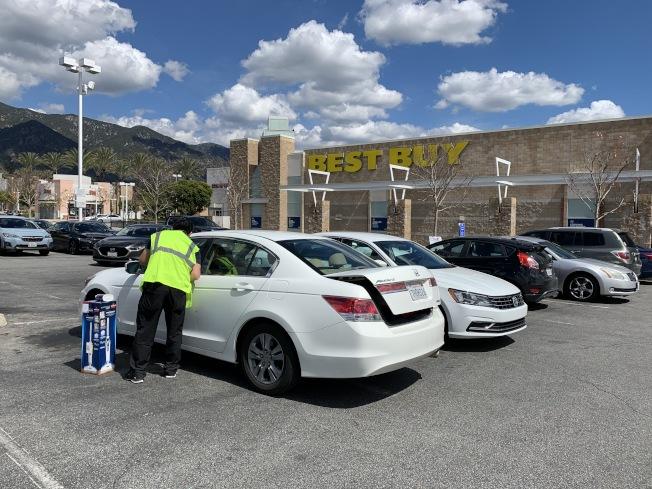 客人停車在百思買商場外,店員推車送貨並放入汽車後備箱內。(記者丁曙/攝影)