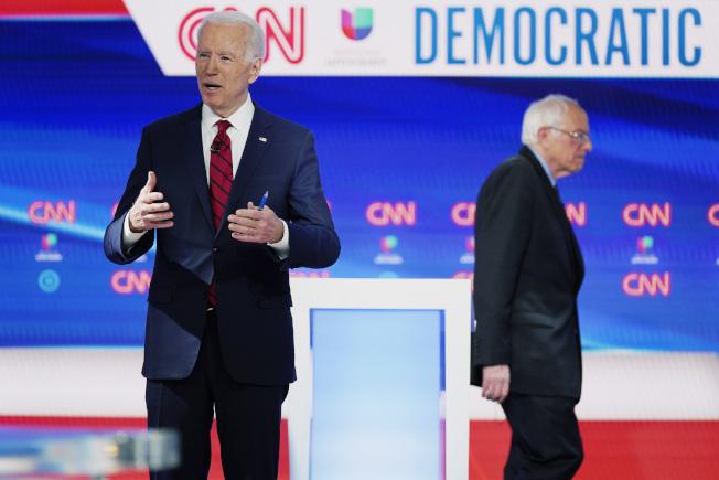 民主黨總統初選參選人桑德斯參議員(右),雖然已明顯輸於白登,但仍不宣布退選。圖為白登(左)與桑德斯加參加電視政見辯論會。(美聯社)