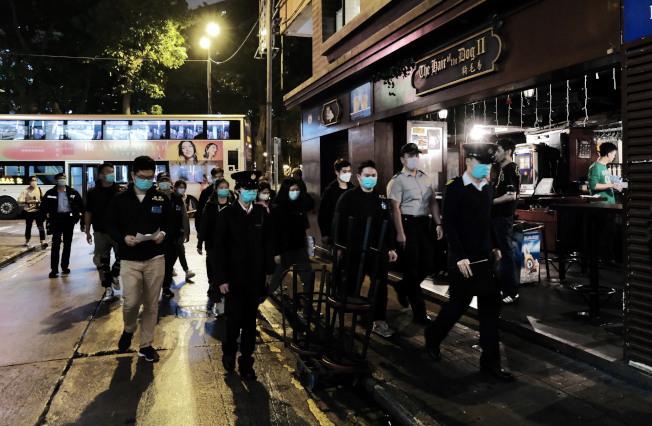 香港「限聚令」一周,港府人員聯同警方到尖沙咀一帶酒吧及餐廳巡查。(中新社)