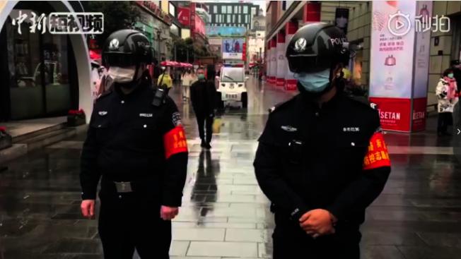 春熙路街頭,頭戴智慧型頭盔的警察正為民眾檢查體溫。該頭盔可完成對前方5米範圍內所有目標人員的掃描,若發現體溫超過37.3度,頭盔立刻聲光報警。(秒拍影音)