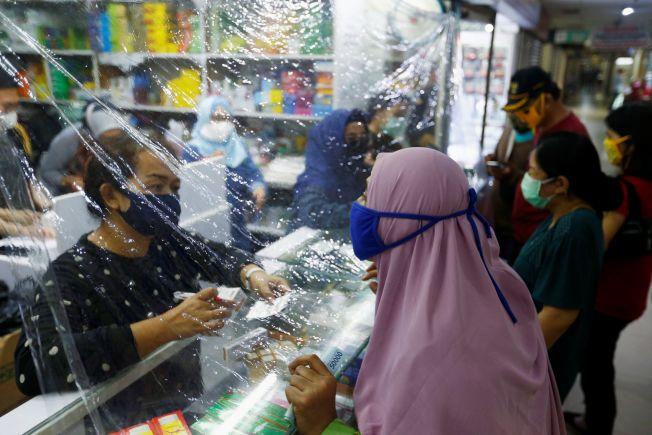 印尼下令所有人外出均須戴口罩,圖為雅加達一間商家用塑膠膜來進行防疫的畫面。(路透)