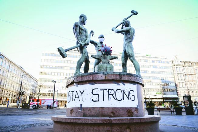 芬蘭首都赫爾辛基的三鐵匠雕像下貼了「要堅強」標語。芬蘭長年儲備的醫療物資,在這次新冠肺炎疫情中發揮作用。(歐新社)