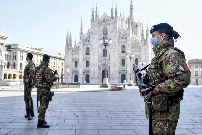 歐陸的西班牙與義大利冠病毒疫情似打緩和跡象。圖為義大利米蘭大教堂前戴著口罩的戒備部隊,廣場上沒有遊人。(美聯社)