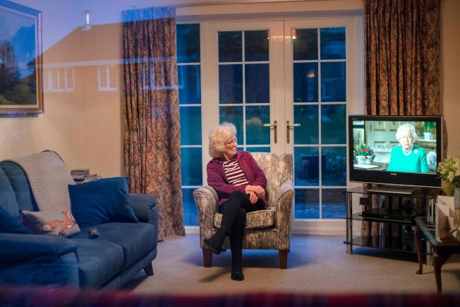 英國民眾在家中觀看女王伊麗莎白二世的特別演說。(美聯社)