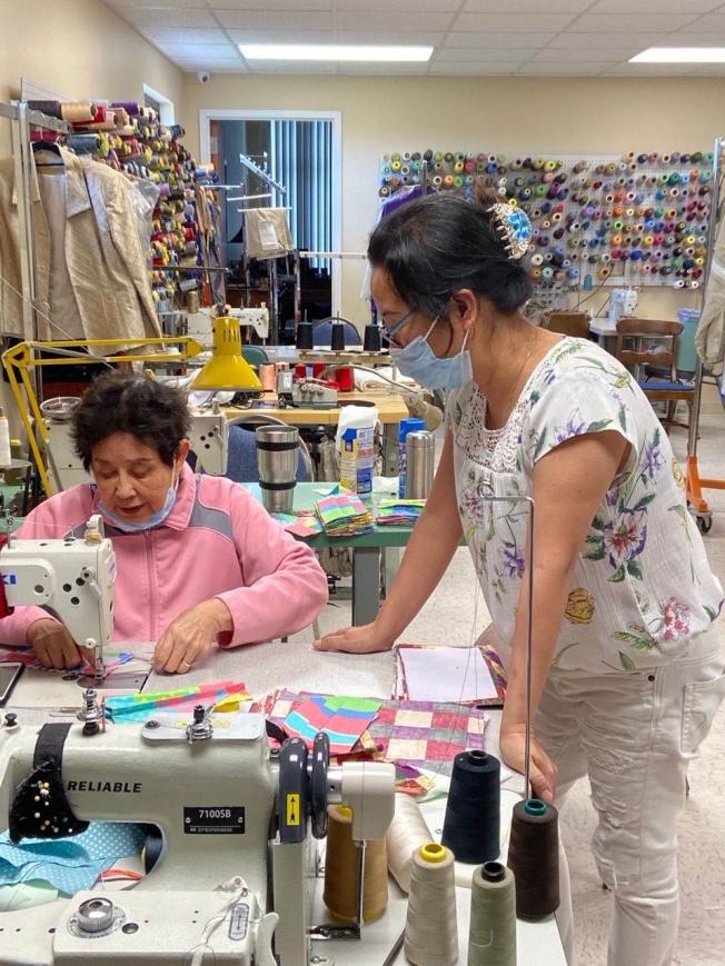陳少娟(左)和志工一起在其所經營的裁縫店製作愛心口罩。