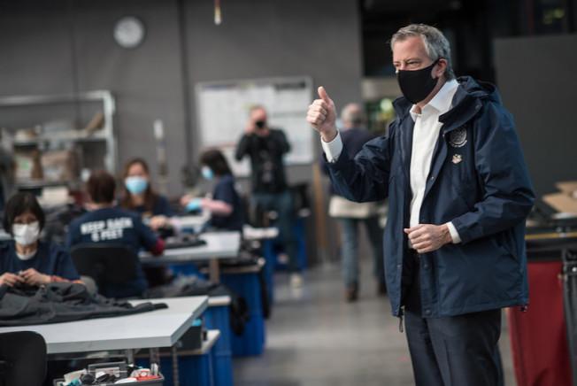 白思豪戴口罩視察防護服臨時工廠時致敬華人工人,感謝他們背負歧視卻仍努力工作。(市長辦公室提供)
