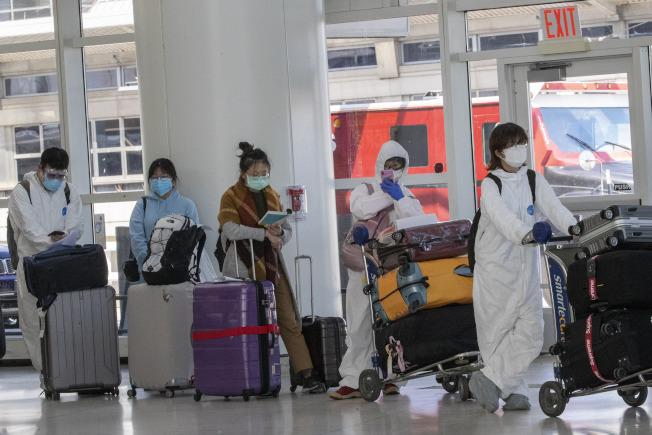 3月24日,紐約甘迺迪國際機場(JFK),準備登機的乘客戴著口罩和防護服。(美聯社)