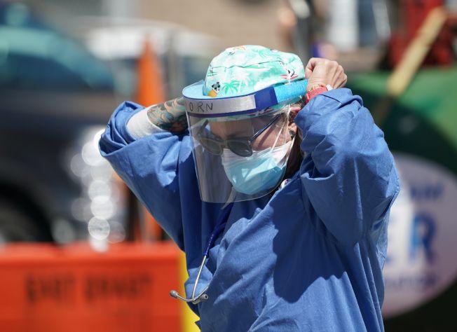紐約布魯克林,一位護士走出醫院,整理防護服。(Getty Images)