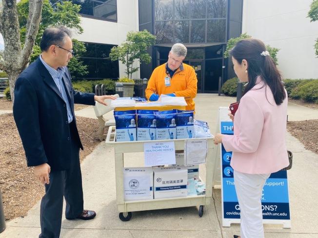 國際領袖基金會顧問曲曉燕(右一)、華醫協會會長王翔(左一)送防護服到被指定為新冠急救中心的UNC Rex醫院。(陳海娜提供)