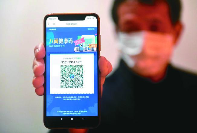 滯留湖北的群眾與本地人必須出示手機上的「健康碼」才能出行。(中新社)